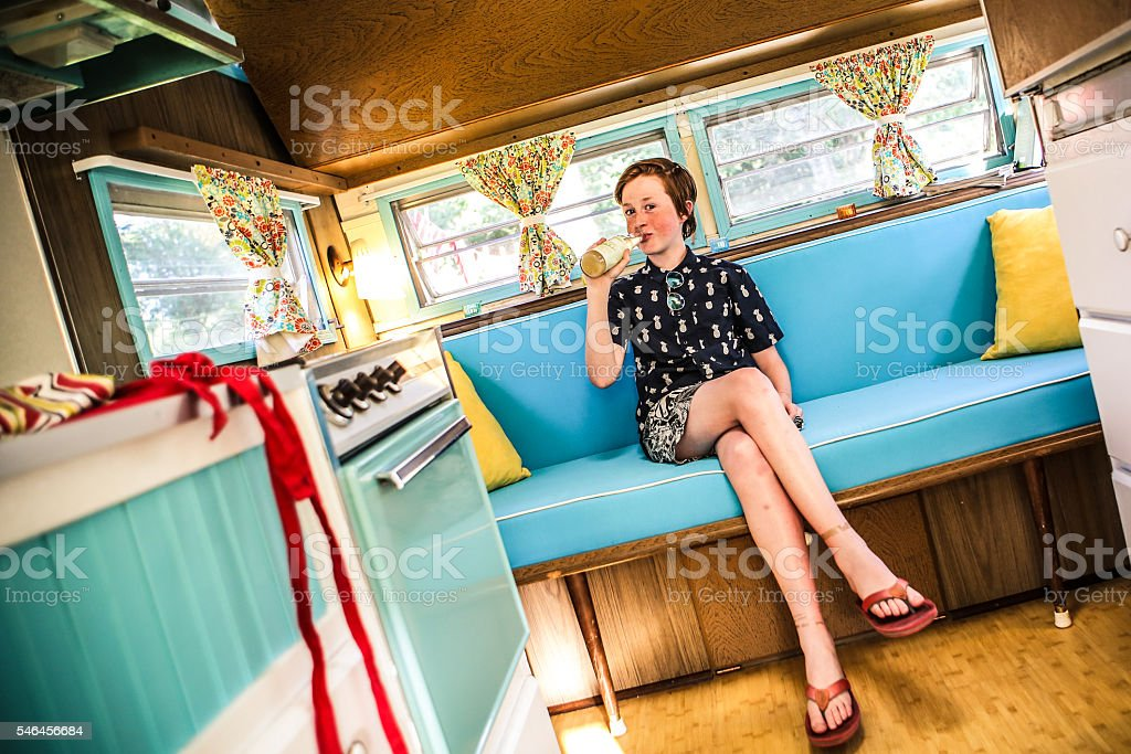 Adorable Young Teen Drinking Soda in Restored Vintage Camper Trailer stock photo
