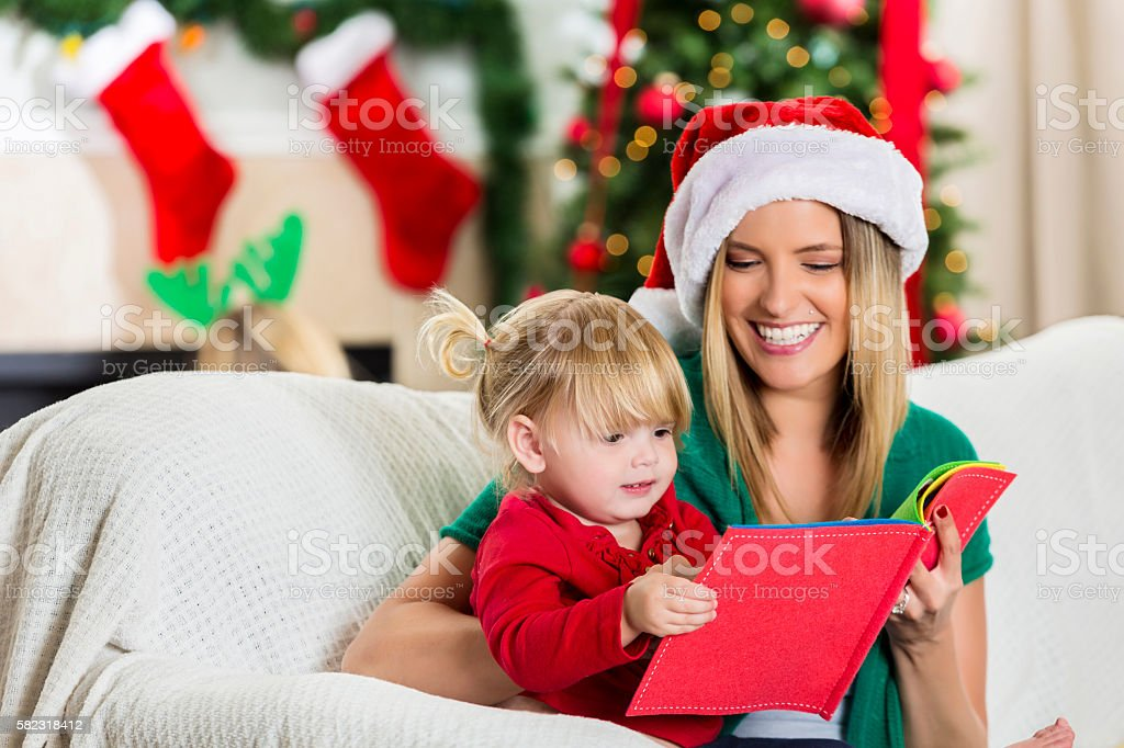Adoring mom reads book with toddler daughter stock photo