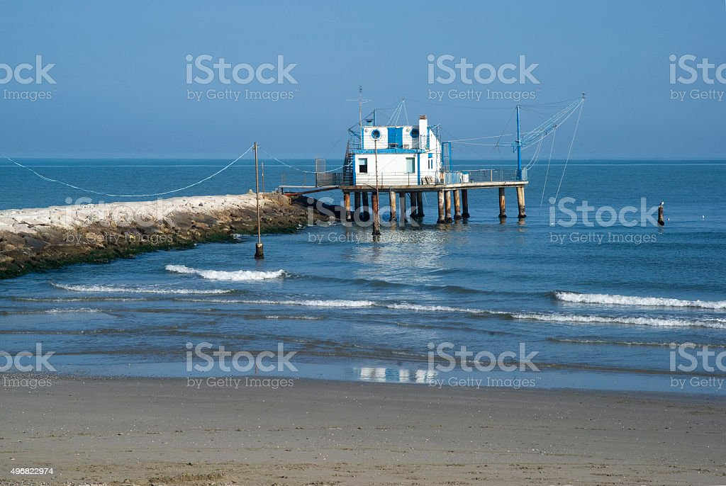 Adriatic, Italy. Stilt house by the sea and fishing nets stock photo