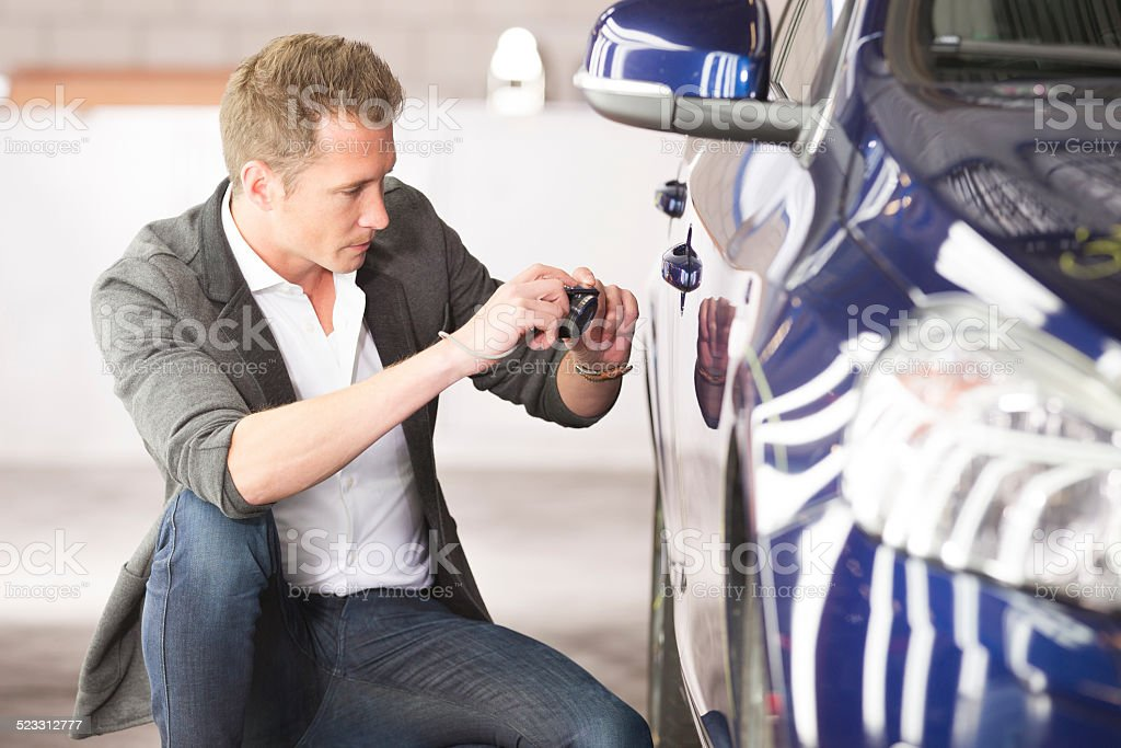 Adult accessor looking at car, estimate for fix stock photo