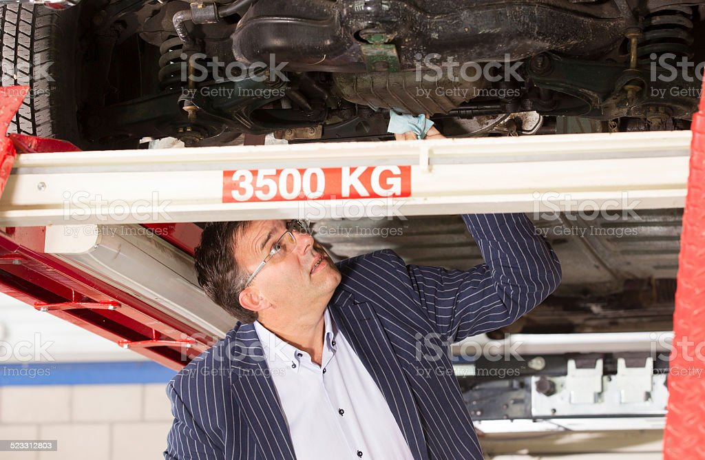 Adult accessor under old car estimate for fix stock photo