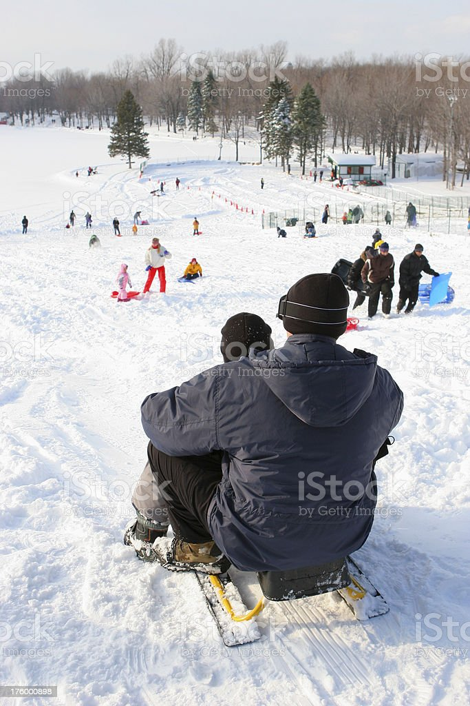 Adult and child getting ready for a snow slide royalty-free stock photo