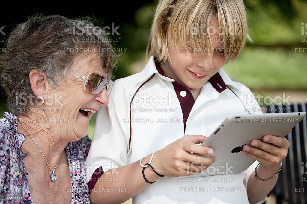Adult and child smiling looking at an iPad 2 together royalty-free stock photo