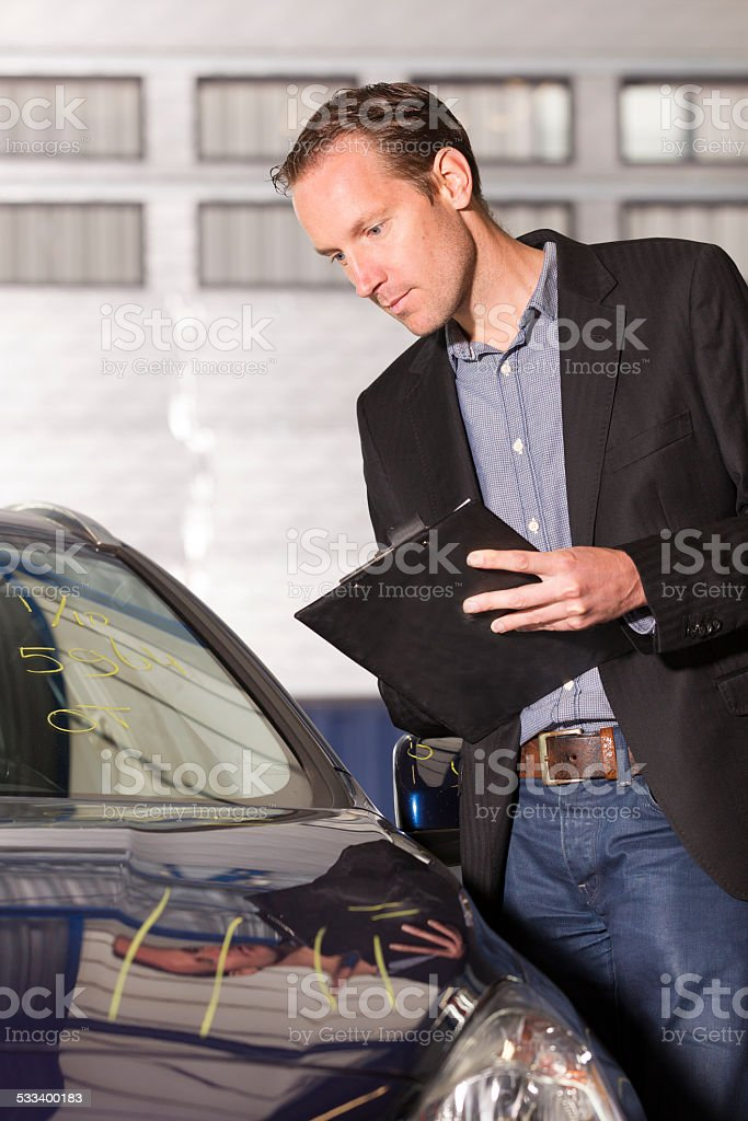 Adult appraiser looking at car, estimate for fix stock photo