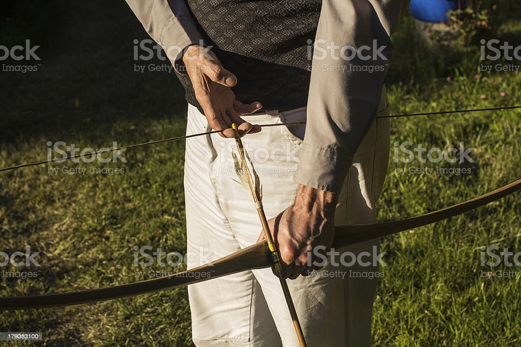 Adult archer preparing Arrow and Bow royalty-free stock photo