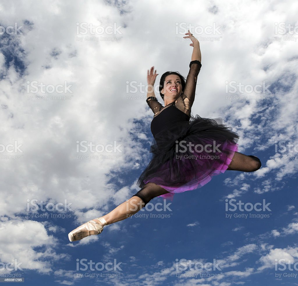 Adult ballerina leaping through the air outdoors royalty-free stock photo