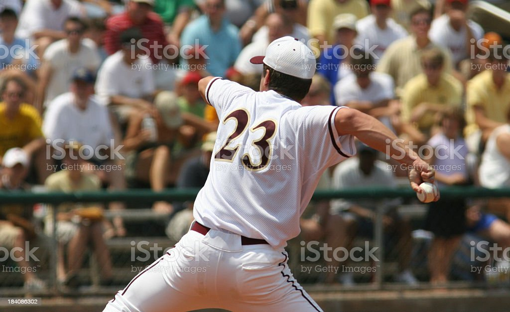 Adult baseball pitcher with spectators in background stock photo