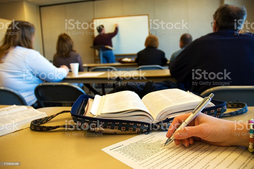 adult bible study class watches the instructor at a whiteboard stock photo