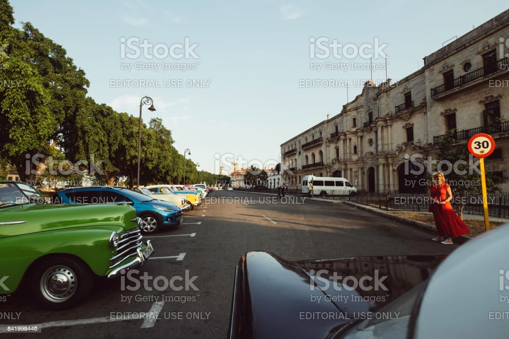 Adult blonde woman in red dress with bright colored classic cars and a street sign stock photo