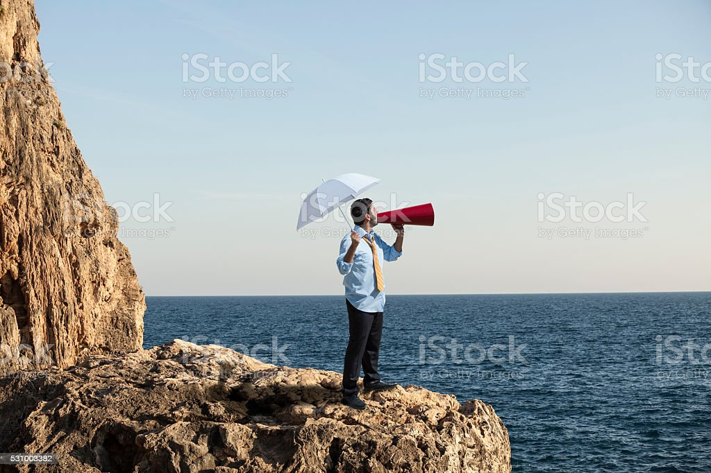Adult Businessman Standing On The Cliff And Shouting With Megaphone stock photo