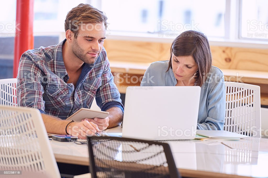 Adult caucasian man and woman working beside each other stock photo