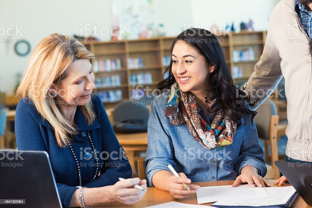 Adult college student talking to professor or classmate in library stock photo