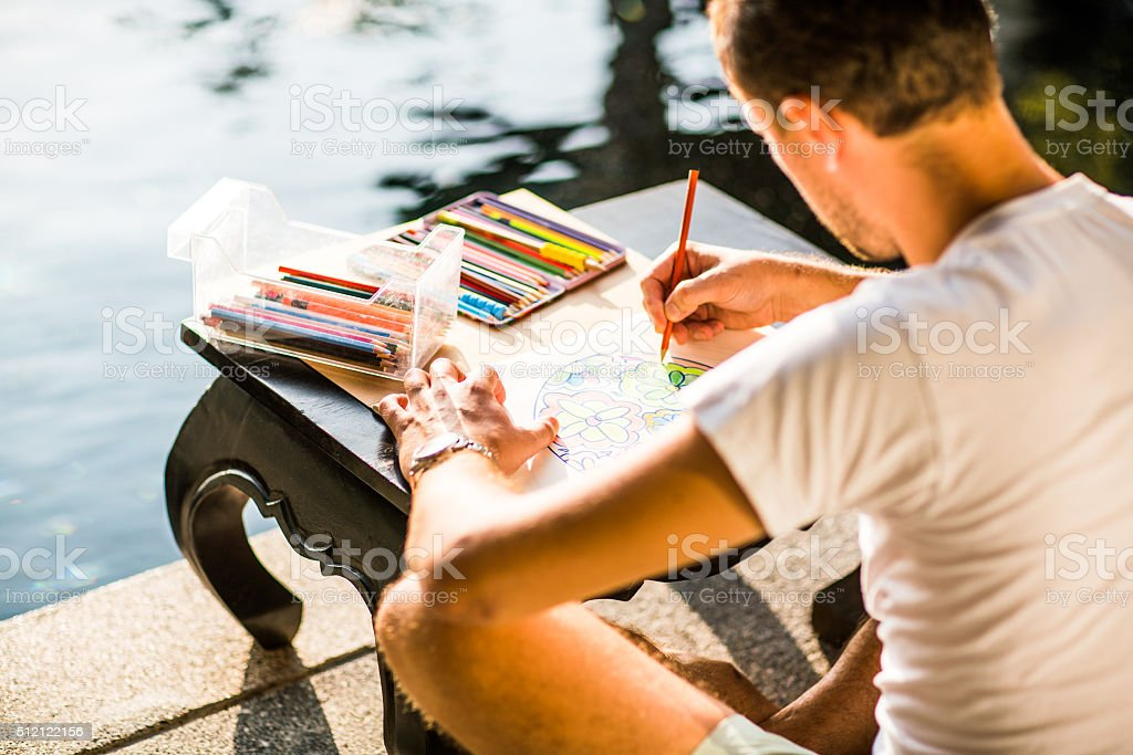 Adult colouring with soft tip pencils, designer, handsome men stock photo