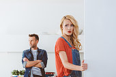 Adult couple after argument, focus on worried woman