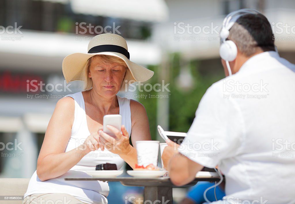 Adult couple at table using devices stock photo