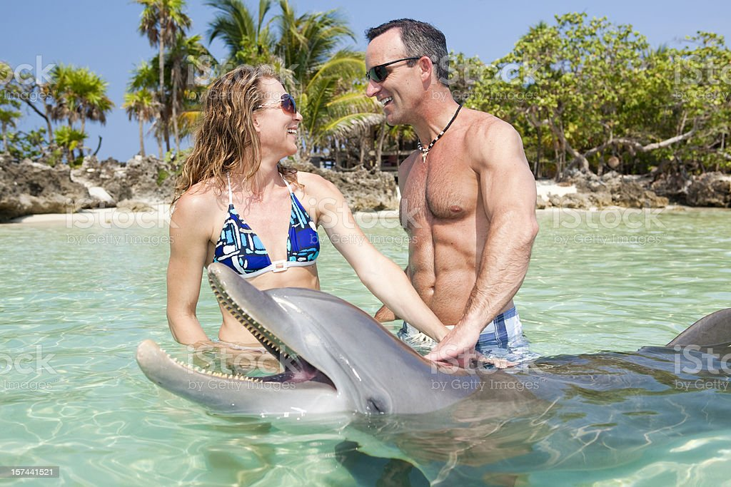 Adult couple enjoying time in water with a dolphin stock photo