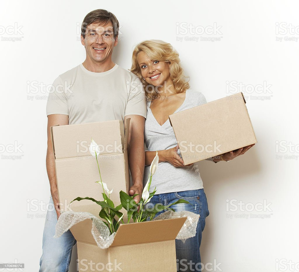 Adult couple moving into a new home and packing boxes. royalty-free stock photo