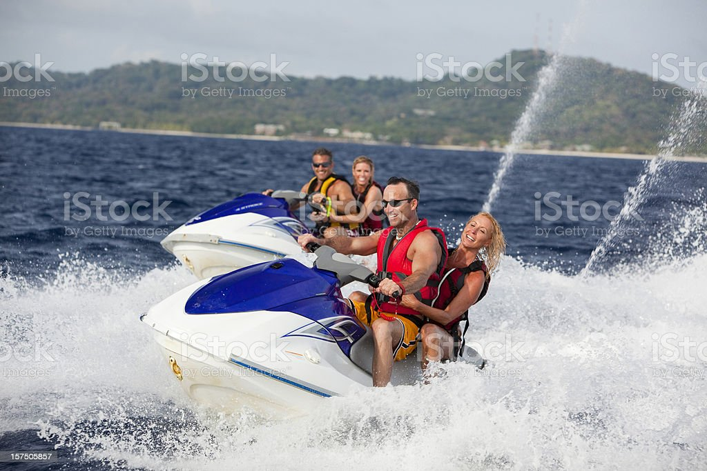 Adult couple riding jet boats stock photo