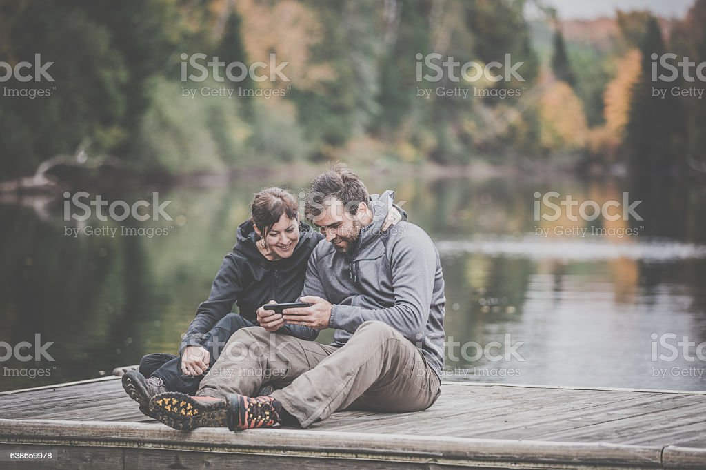 Adult Couple Using Smart Phone in Nature stock photo