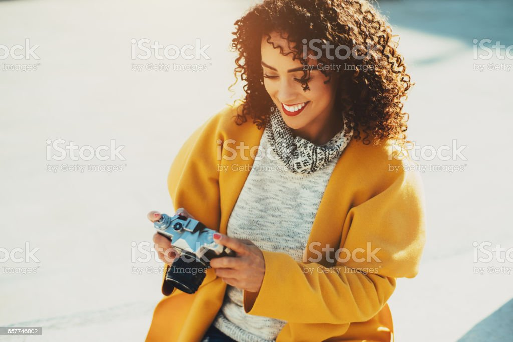 Adult curly brazilian sminling woman with retro camera stock photo