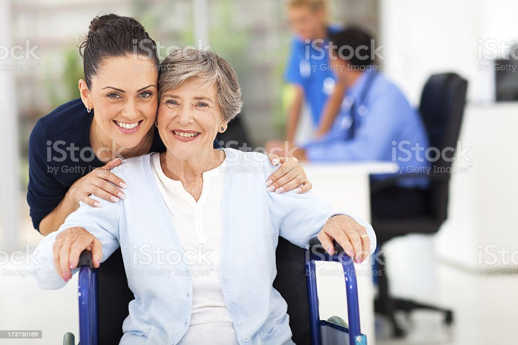 adult daughter accompanying senior mother visiting doctor stock photo