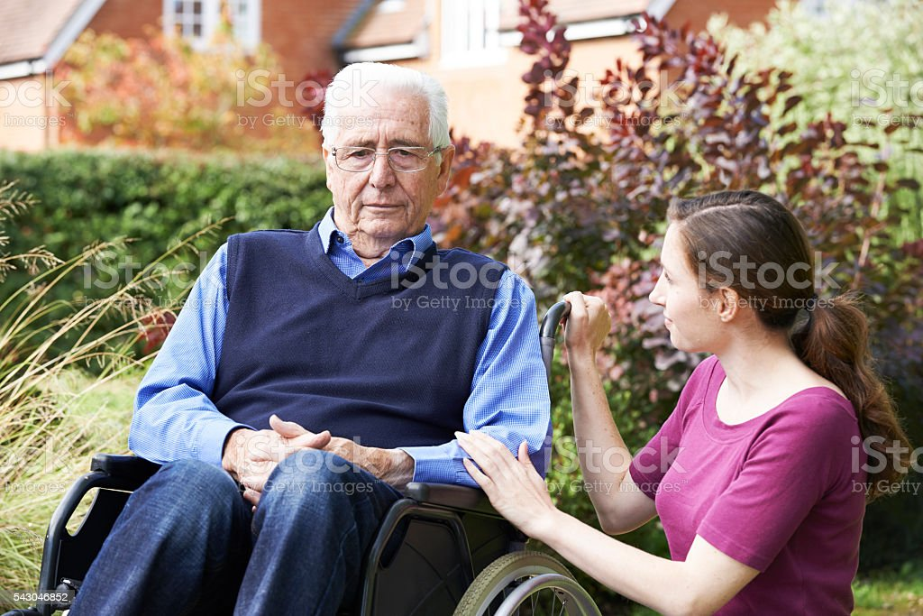 Adult Daughter Comforting Senior Father In Wheelchair stock photo