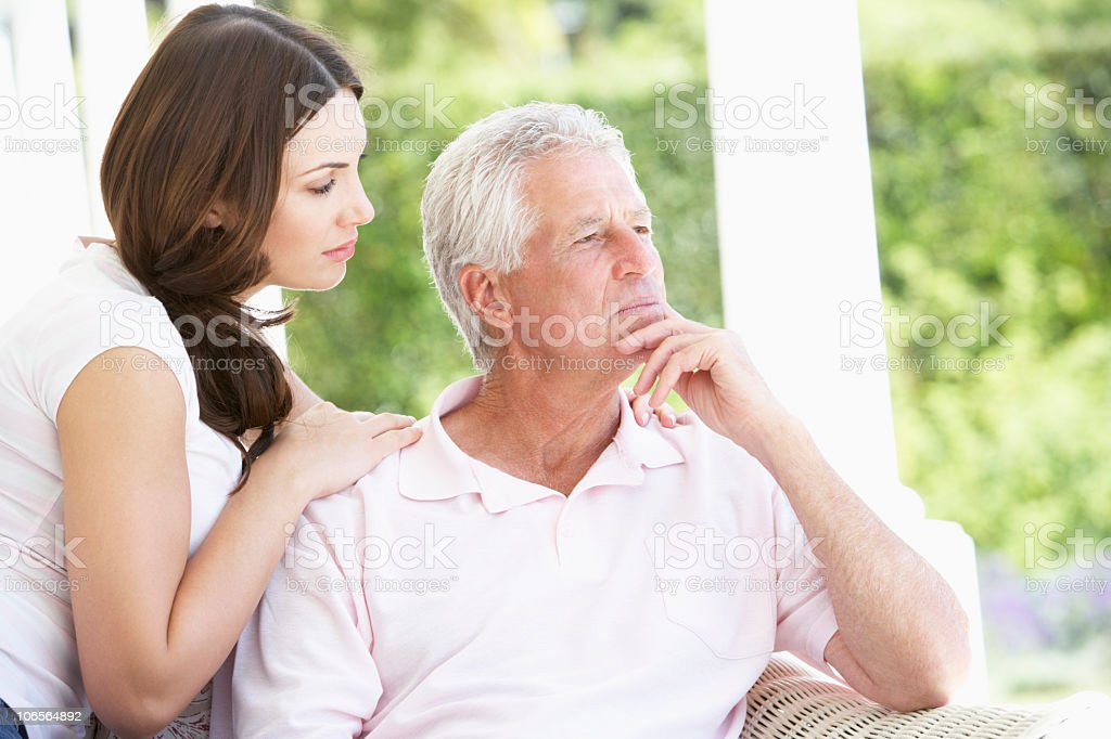 Adult Daughter Comforting Worried Father stock photo