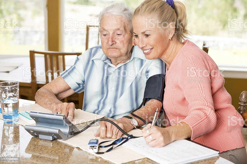 Adult daughter counting out pills for her senior father royalty-free stock photo