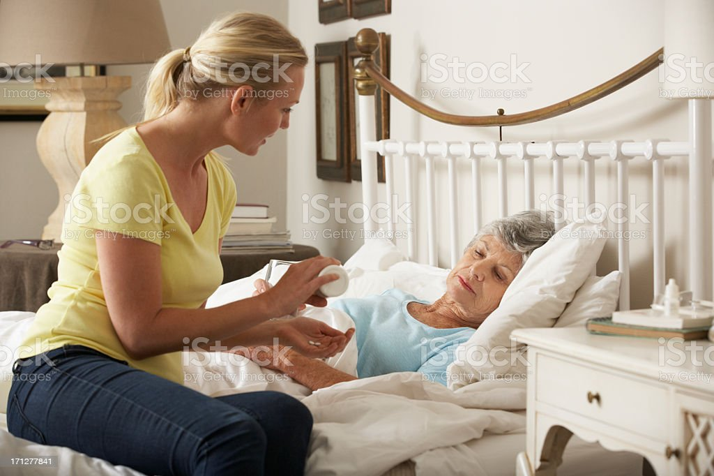 Adult Daughter Giving Senior Female Parent Medication In Bed stock photo