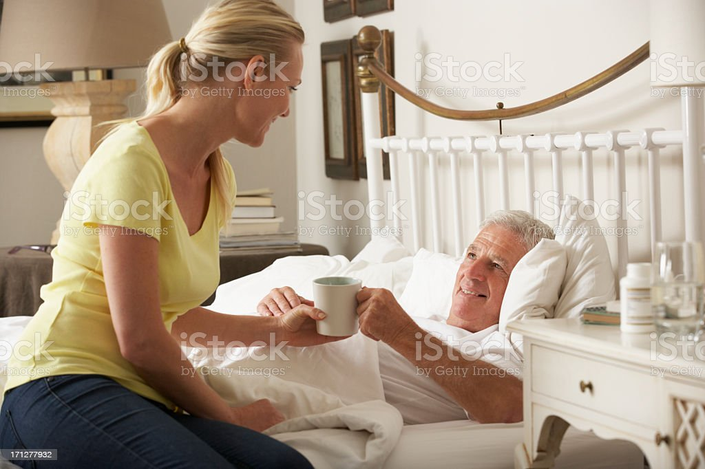 Adult Daughter Giving Senior Male Parent Hot Drink In Bed stock photo