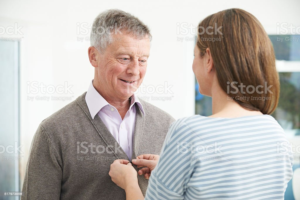 Adult Daughter Helping Senior Man To Button Cardigan stock photo