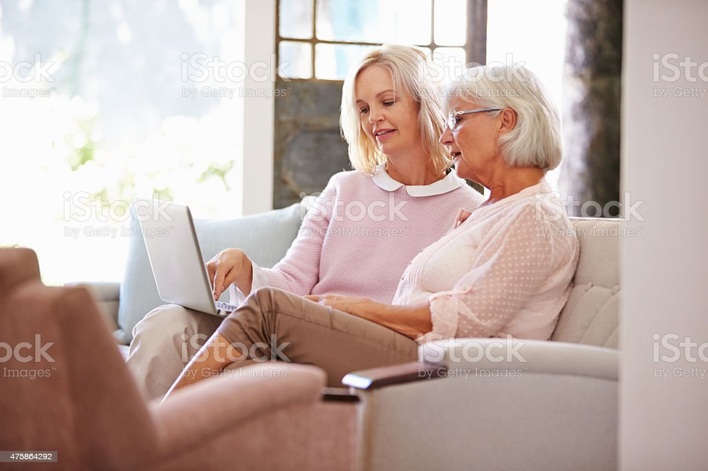 Adult Daughter Helping Senior Mother With Computer At Home stock photo