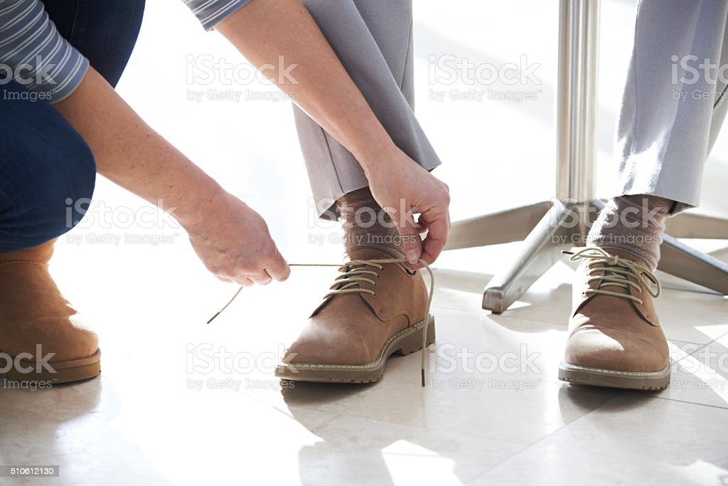Adult Daughter Helping Senior Tie Shoelaces stock photo
