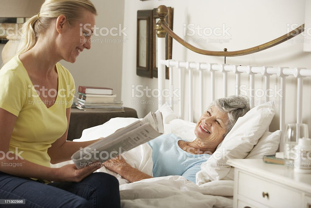 Adult Daughter Reading Newspaper To Senior Female Parent stock photo
