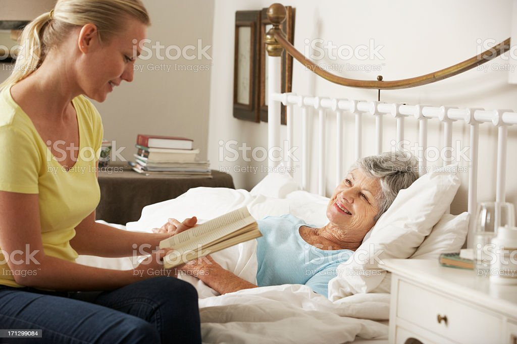 Adult Daughter Reading To Senior Female Parent In Bed stock photo