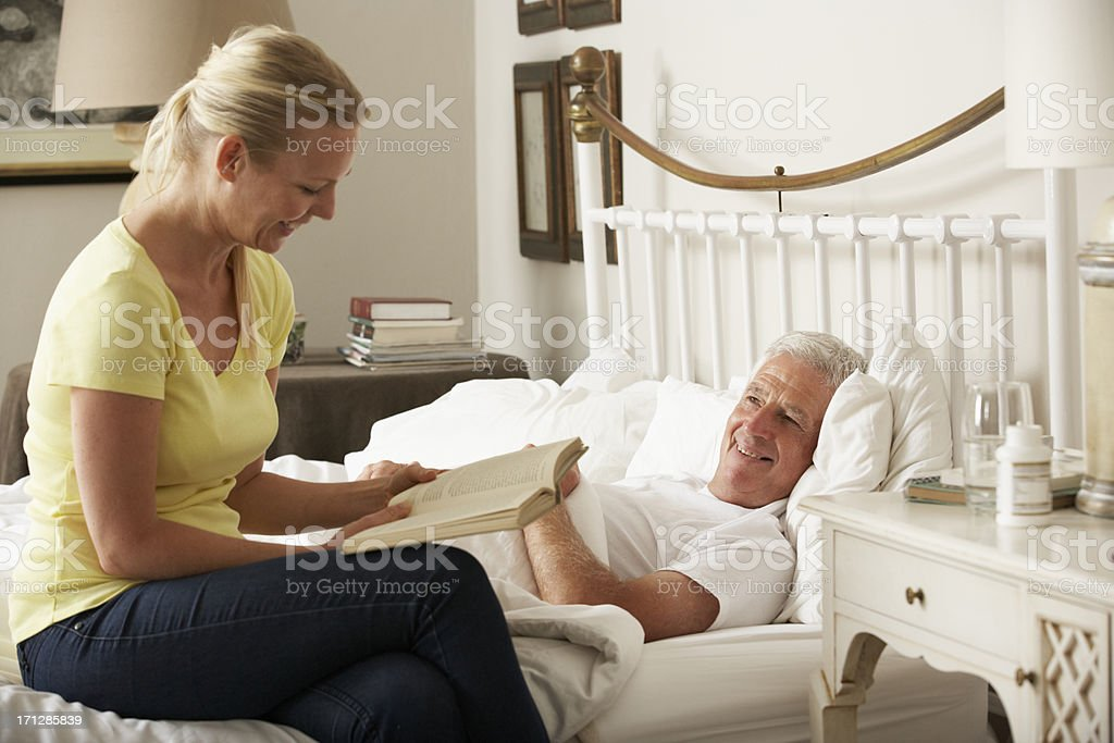 Adult Daughter Reading To Senior Male Parent In Bed stock photo