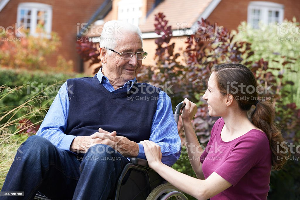 Adult Daughter Visiting Father In Wheelchair stock photo