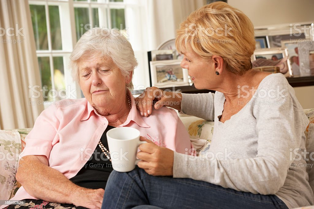 Adult Daughter Visiting Unhappy Senior Mother Sitting On Sofa stock photo