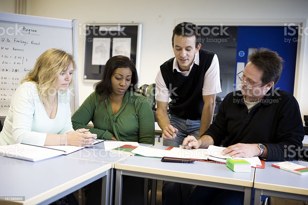 adult education: a teacher helping a group of mature students royalty-free stock photo