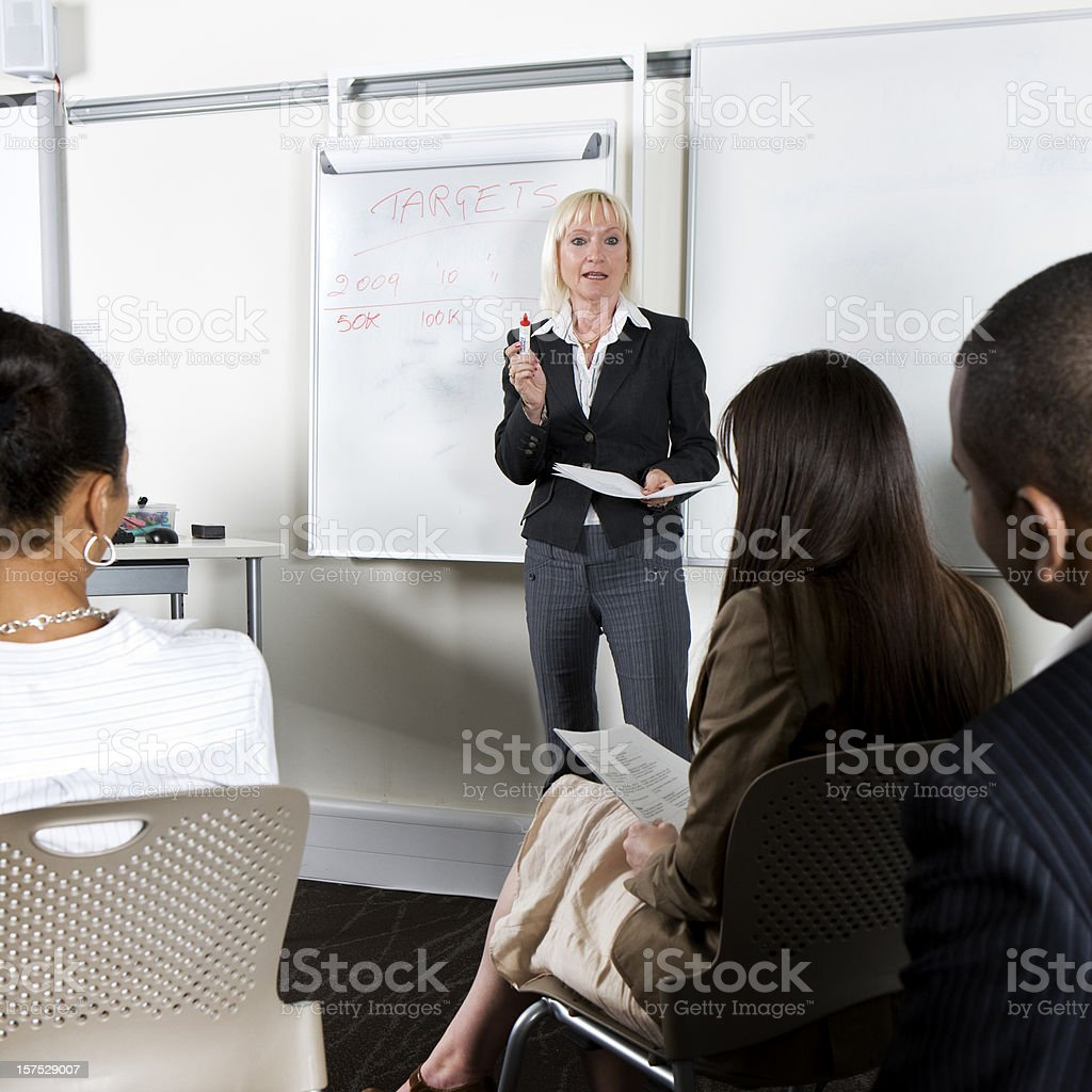 adult education business studies: teacher addressing her class royalty-free stock photo