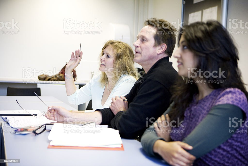 adult education: mature student raising her hand to question teacher royalty-free stock photo