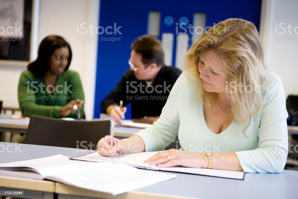 adult education: mature student writing at her desk royalty-free stock photo