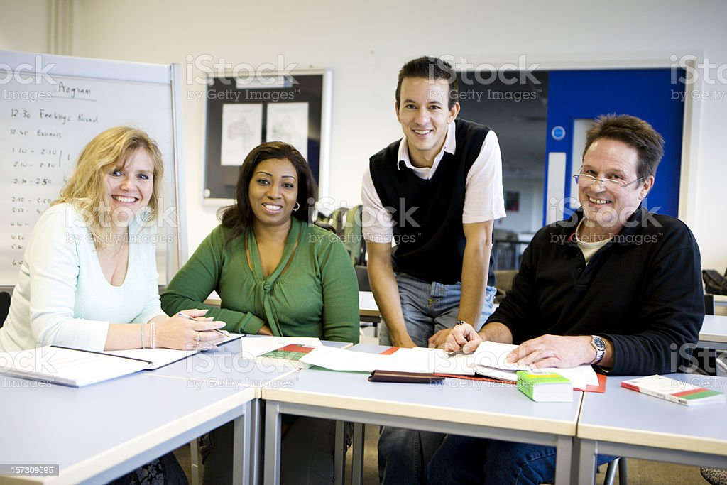 adult education: mature students and their teacher in the classroom stock photo