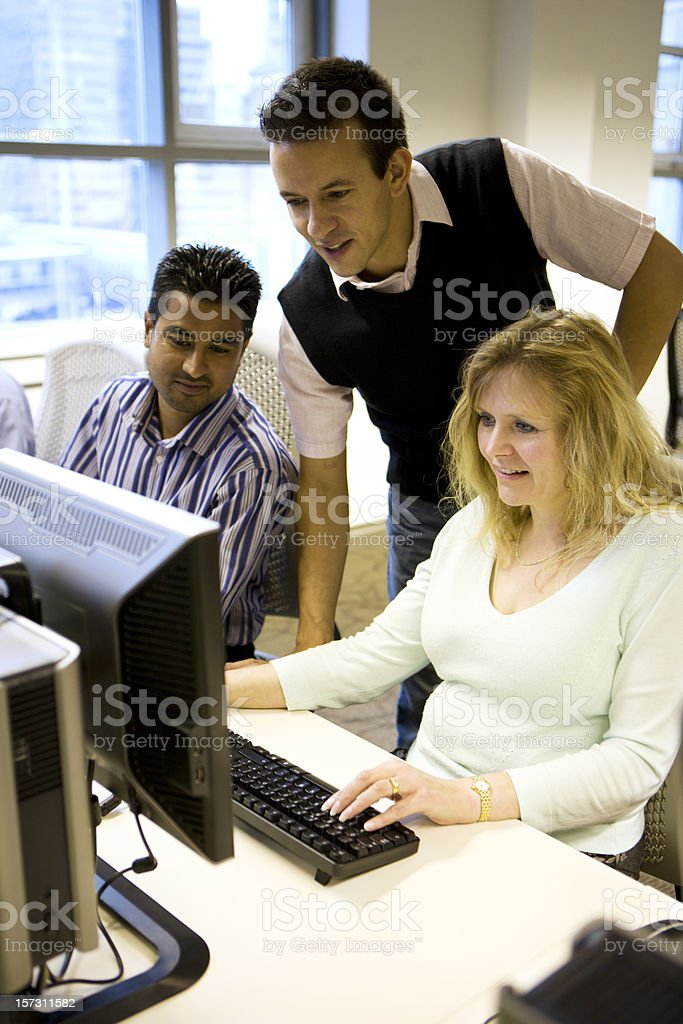 adult education: Office colleagues working together at the computer royalty-free stock photo
