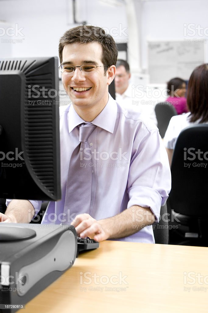 adult education: Smiling office professional at his desk royalty-free stock photo