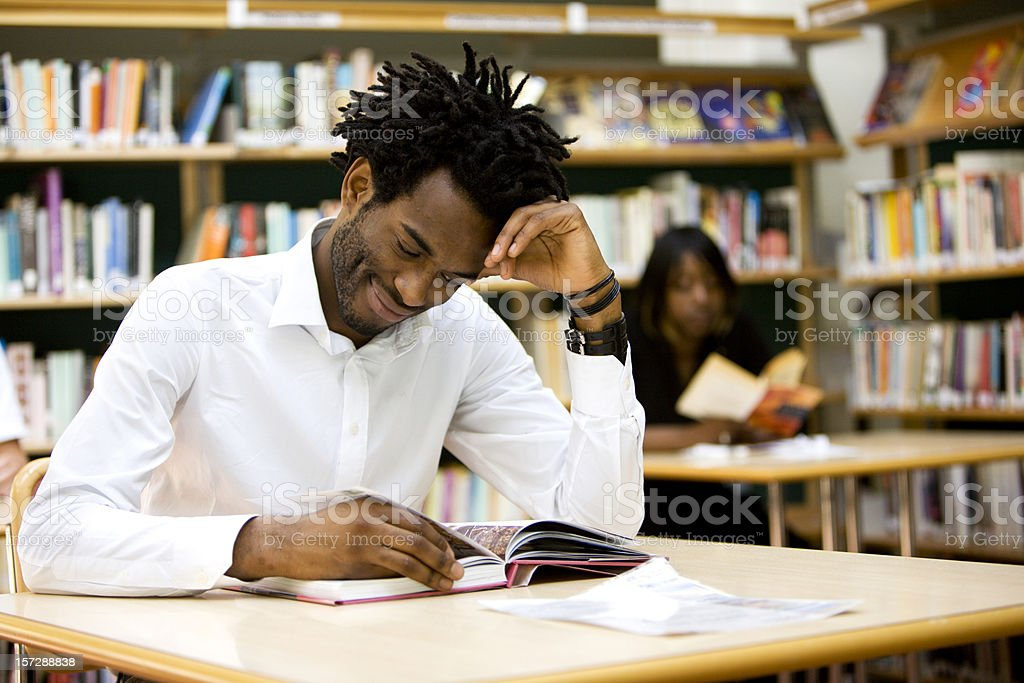 adult education: university student reading in his college library royalty-free stock photo
