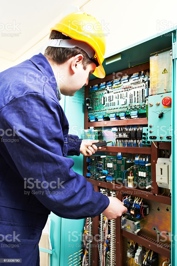 adult electrician builder engineer worker testing electronics in switch board stock photo