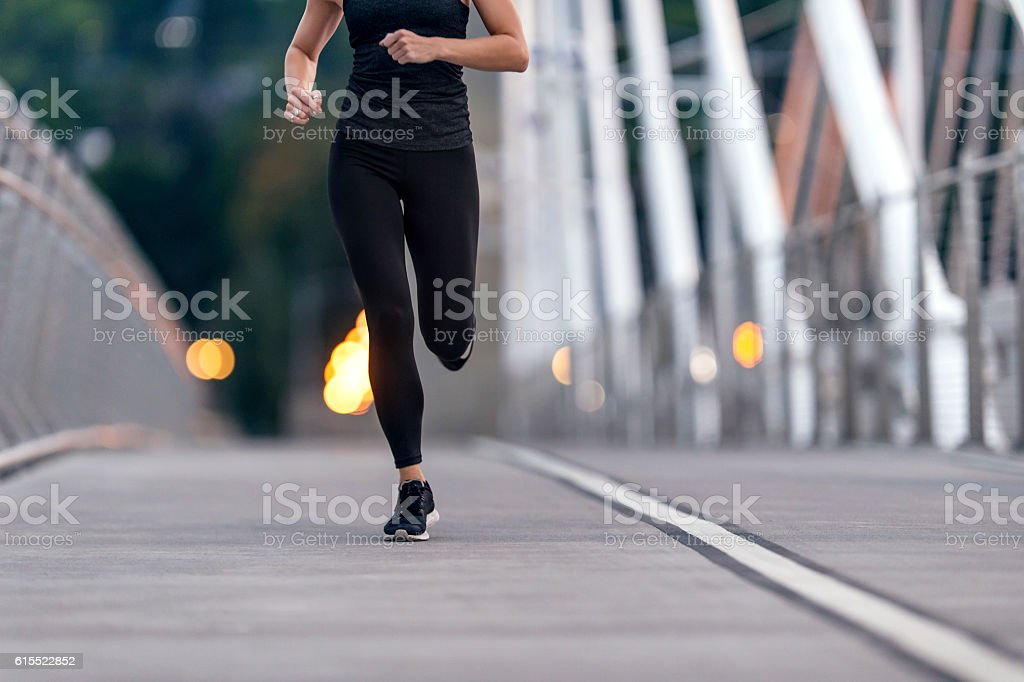 Adult female athlete figure running across a bridge stock photo
