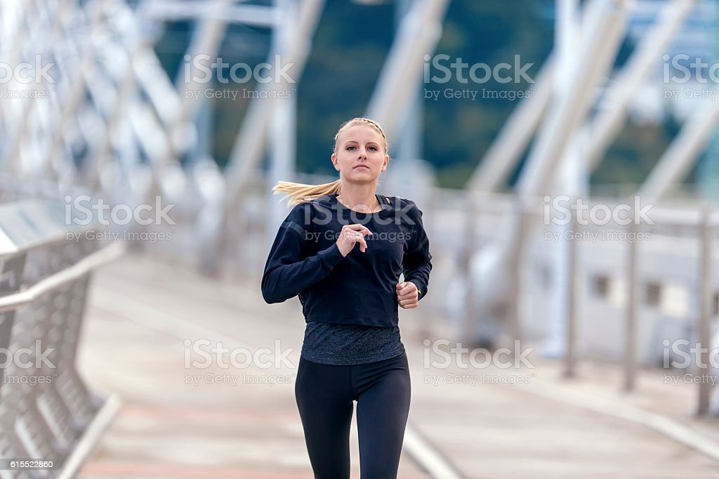 Adult female athlete jogging across a bridge stock photo