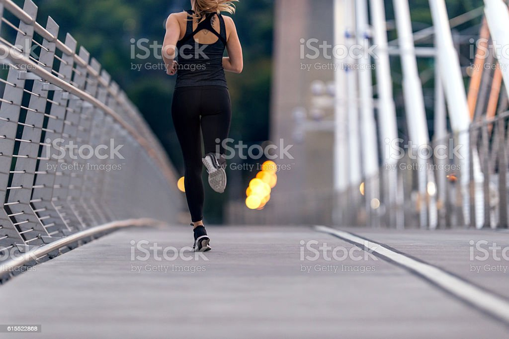 Adult female athlete person running across a bridge stock photo